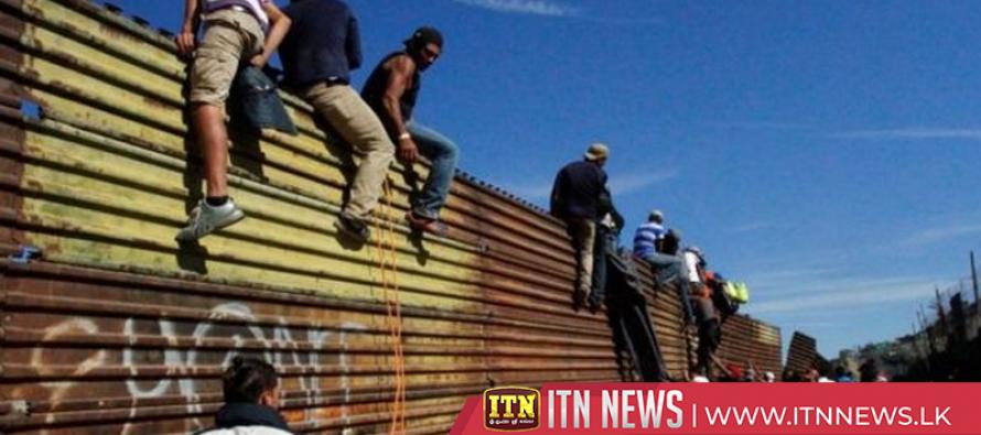 Migrants in Mexico climb over border fence in dash towards the U.S.